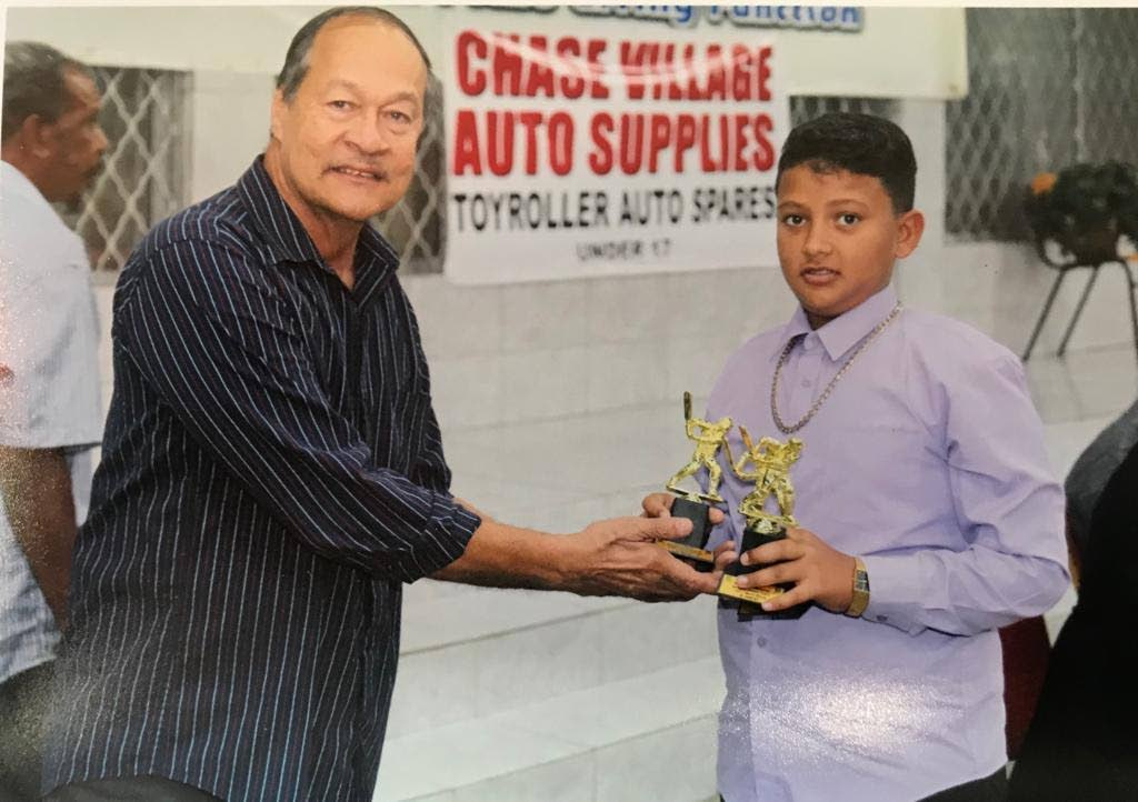 Lambert Lee Ahyen, left, presents an award to Timothy Nathaniel at the Caroni Cricket Association award giving function at Presentation College, Chaguanas on January 12.