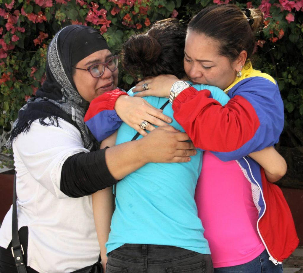Dexis Carolina Rosas, centre, is embraced by Martha Tovar, left, and Carolina Gomez at a press conference held in Mt Lambert to highlight the plight of Venezuelan and other refugees on January 18.    PHOTO BY ANGELO M  MARCELLE