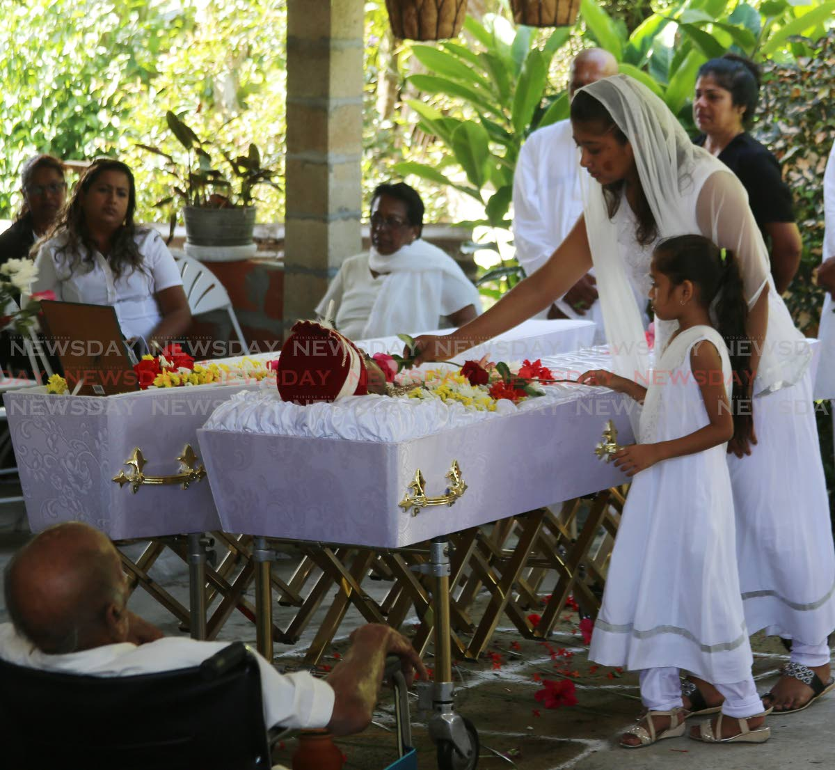 Nikesh Singh, with her daughter Rianna Singh, places flowers in the coffin at the funeral of her husband at Suchit Trace , Penal this morning.  Photo by Vashti Sing
