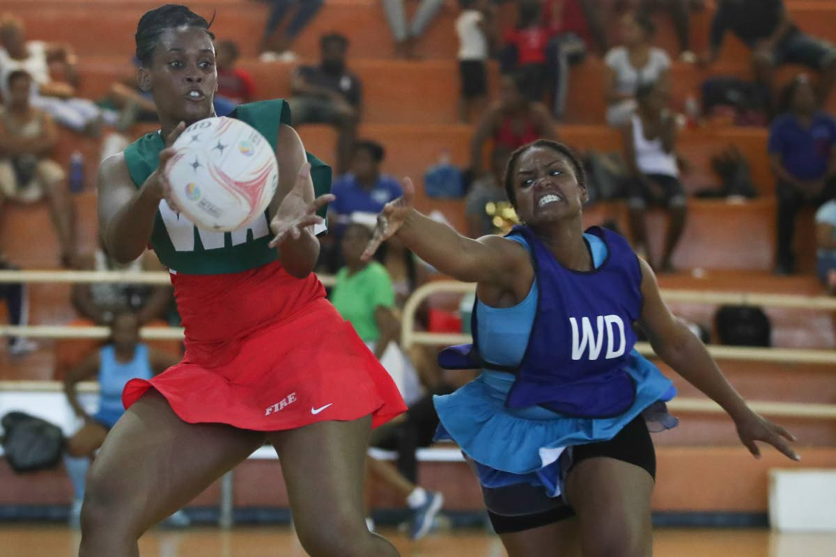 Fire's wing-attack Jellene Richardson, left, collects a pass as Police's Stacy Pilgrim tries to intercept in a Courts All Sectors Netball League at the Eastern Regional Indoor Sports Arena, Tacarigua. PHOTO BY KERLON ORR/CA-IMAGES