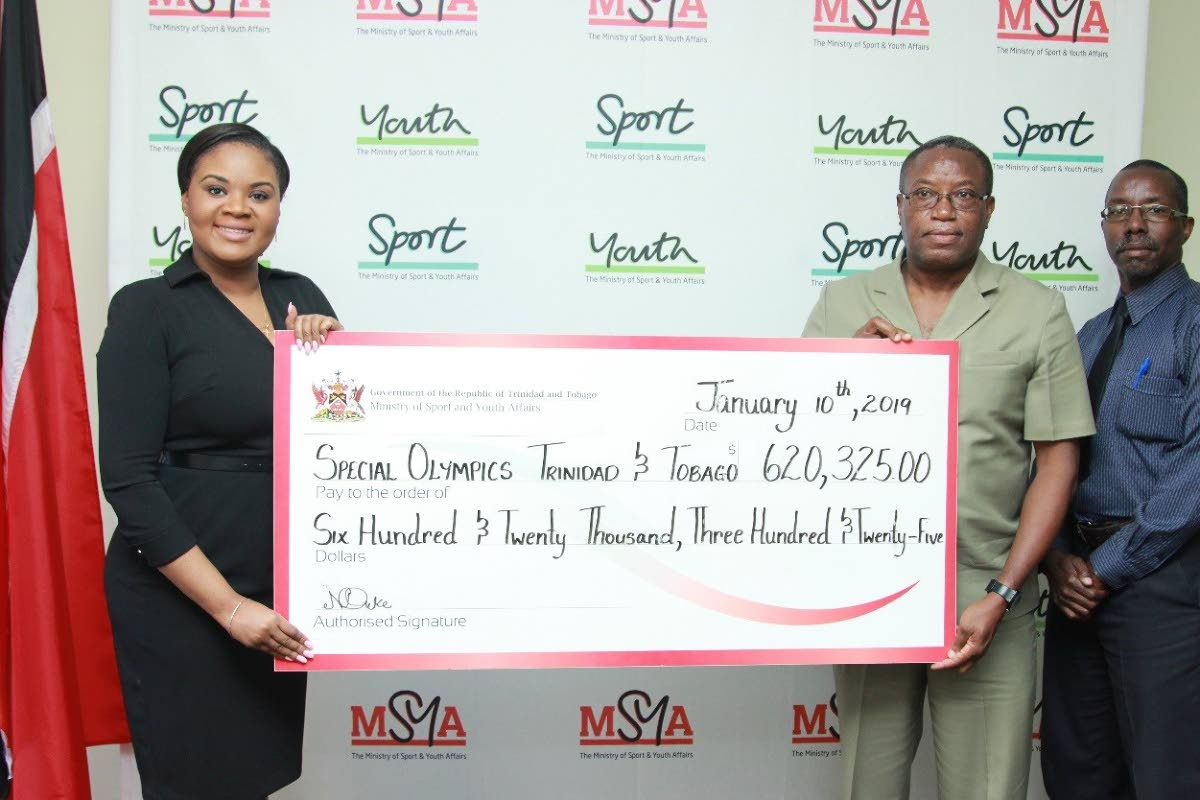 Sports Minister Shamfa Cudjoe, left, presents a cheque to Special Olympics TT national director Ferdinand Bibby, as Patrice Charles, the sports ministry's director of physical education and sport looks on.