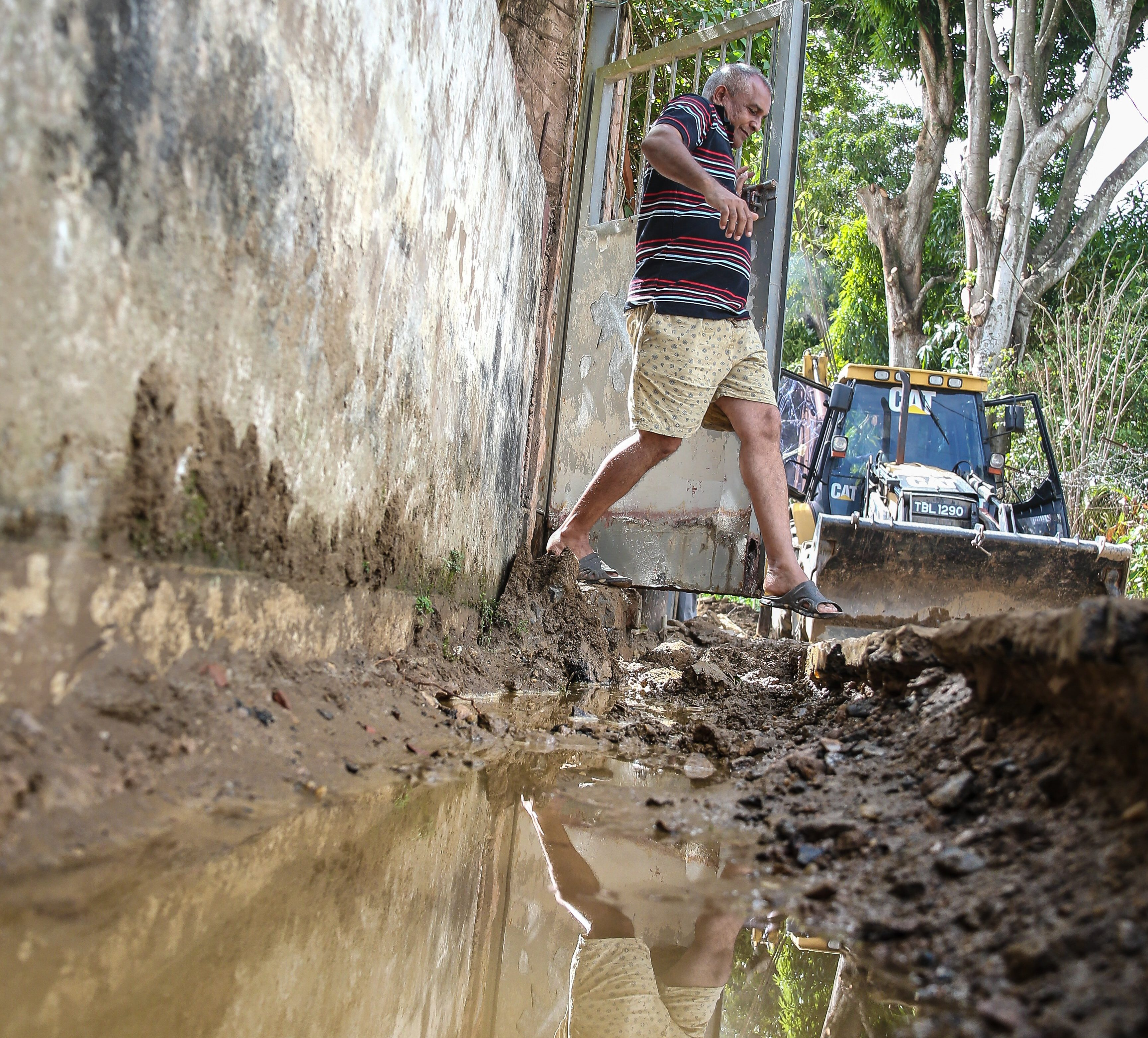 Diego Martin resident, Patrick Maharaj, leaps over an open trench to leave his house.  He is upset over the drain being built without any consultation from the MOWT Drainage Division being held with the residents of Surprise Lane, Diego Martin.  Jeff K. Mayers