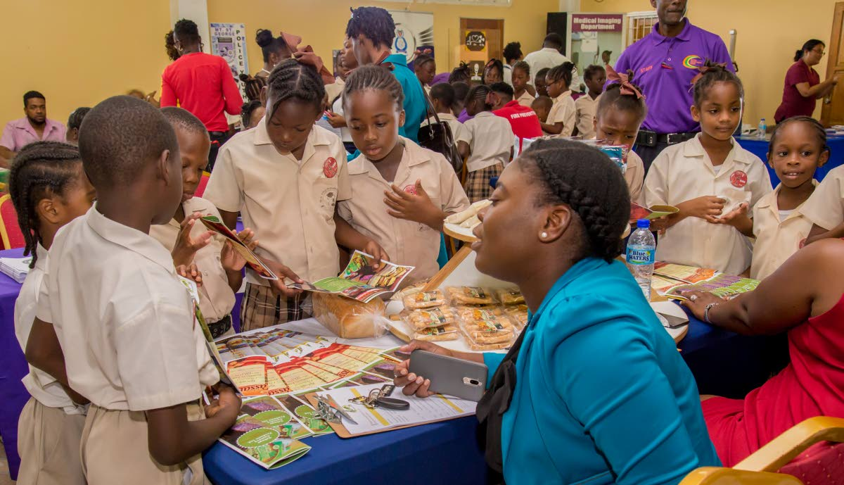 Students of the Mt St George Methodist Primary School learn about products made by the Tobago Cassava Products Ltd at the YES Community Career Expo at the  Mt St George Community Centre last Thursday.