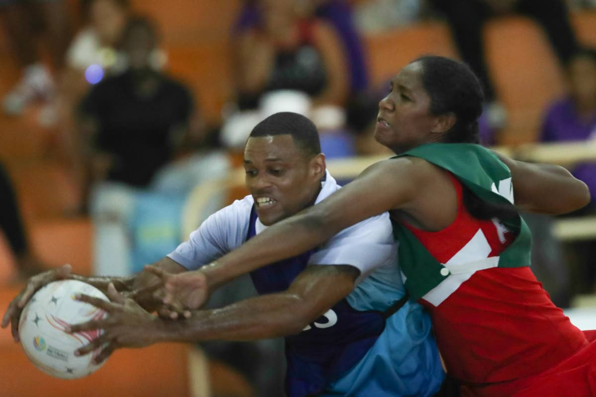 Police's wing-attack Steve Mc Sween, left, receives a pass while defended by Fire's goalkeeper in a Courts All Sectors Netball League match recently at Eastern Regional Indoor Sports Arena, Tacarigua. PHOTO BY KERLON ORR/CA-IMAGES