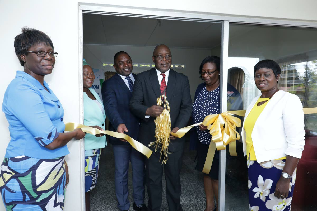 Chief Secretary and Secretary of Education Kelvin Charles, centre, curs the ribbon to open the Learning Enrichment Centre at Hope Farm Road, Hope, on Monday. Others in photo, from left, are Chairman of the Tobago PTA, Denise Nelson-Frank, School Supervisor III Sherry-Anne Rollocks-Hackett, Secretary of Finance Joel Jack, Administrator in Division Jacqueline Job and the Centre's Manager, Suzette Woods-James.