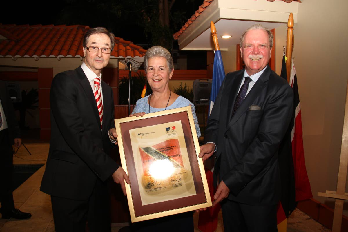 Rhonda Maingot, Co-Foundress of Living Water Community receives the Franco-German Prize for Human Rights and the Rule of Law on behalf of her organisation presented  by the German ambassador Holger Michael, right, and French ambassdor Serge Lavroff, left, the German ambassor residence on Scott Street in St Clair on Tuesday. PHOTO SUREASH CHOLAI