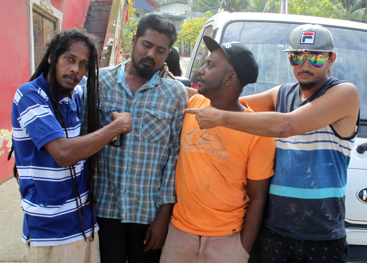 MOURNING: Kishon Kesam Ramnarine (second from left), who survived a boating mishap in which two of his fishing colleagues died at Maracas yesterday morning, is comforted by friends.   PHOTO BY ROGER JACOB