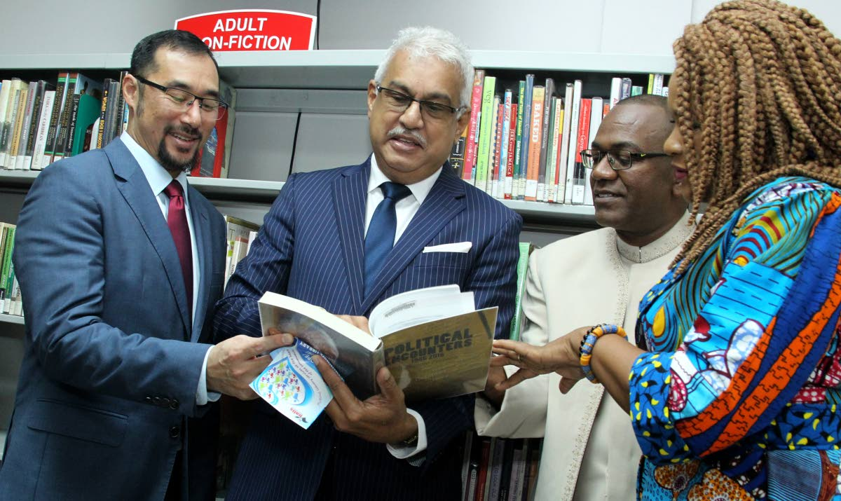 National Security Minister Stuart Young, Health Minister Terrence Deyalsingh, Nalis chairman Neil Parsanlal and Minister of Community Development Culture and the Arts Dr Nyan Gadsby Dolly skim through a book available at the new library at the Mt Hope/Mt Lambert Community Centre on Friday. PHOTO BY ROGER JACOB