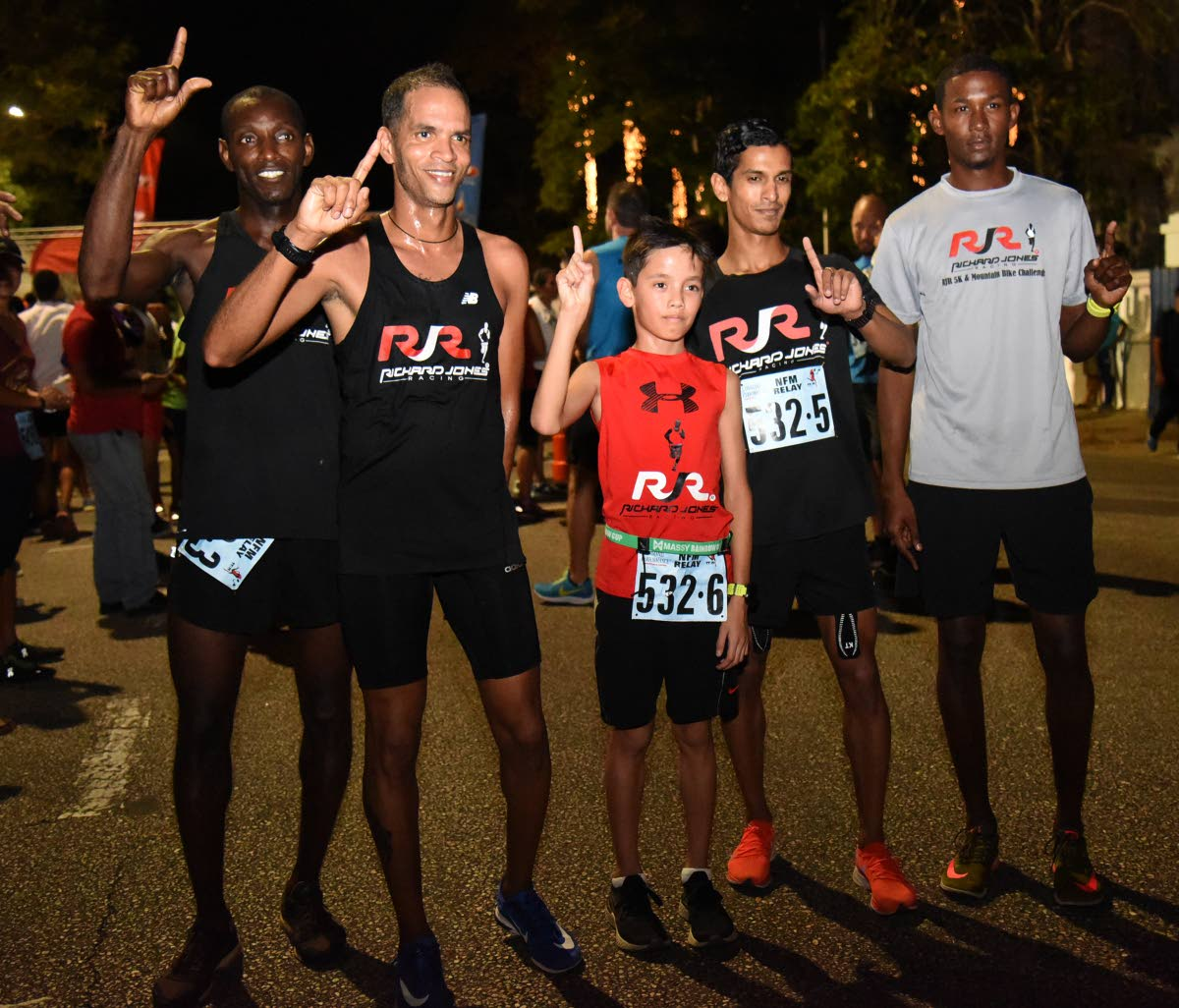 Richard Jones (second from left) and Triston Scott (centre) pose with members of the Richard Jones Racing group after their victory at yesterday's TT International Marathon Relay at the Queen's Park Savannah, Port of Spain.