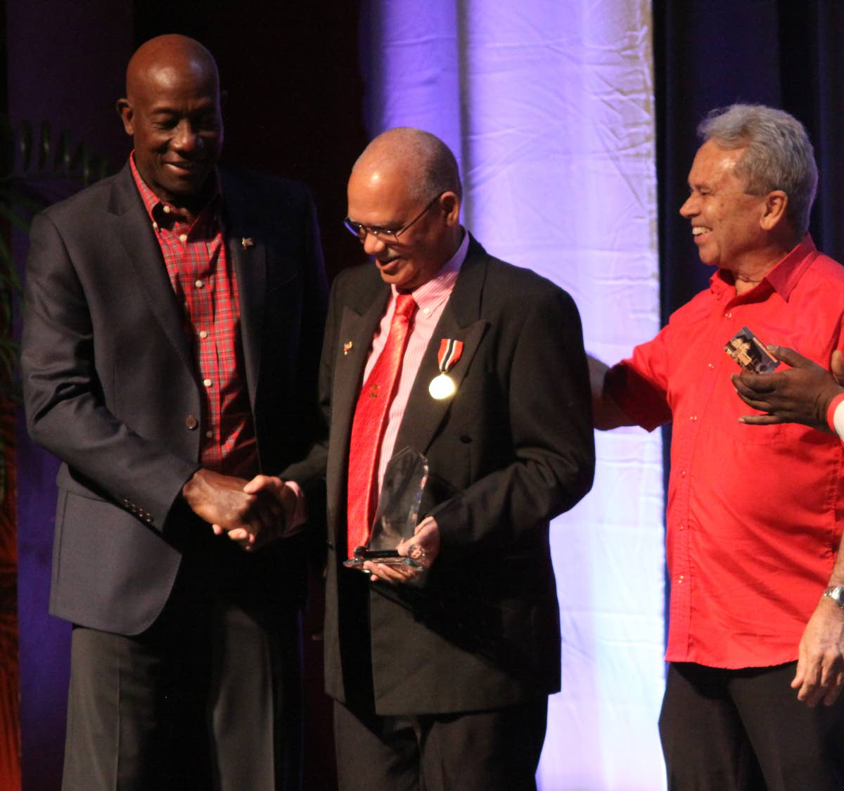 Prime Minister Dr Keith Rowley and Colm Imbert, PNM chairman and Finance Minister, congratulate stalwart Ashton Ford during the party's 63rd anniversary celebrations at NAPA, Port of Spain yesterday. PHOTO BY ANGELO MARCELLE