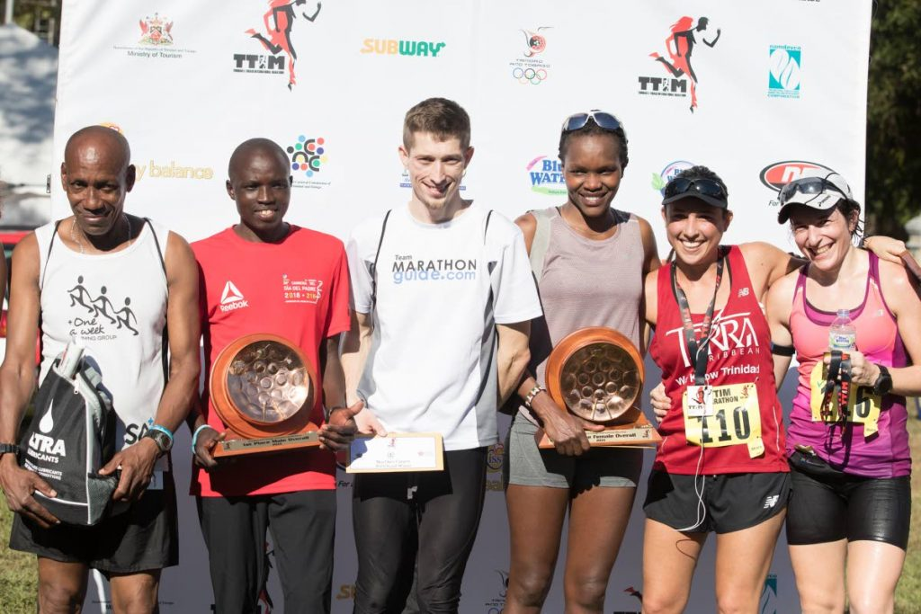 (L-R)Cantius Thomas, the first Trinidadian to cross the finish line stands next to overall winner Kenyan Stephen Njoroge Mbure, second placed Bryan Morseman, of the USA, first female winner Grace Kahura, first Trinidadian female Sjaelan Evans and third placed female runner Allie Adam after they competed at the TT International Marathon yesterday.