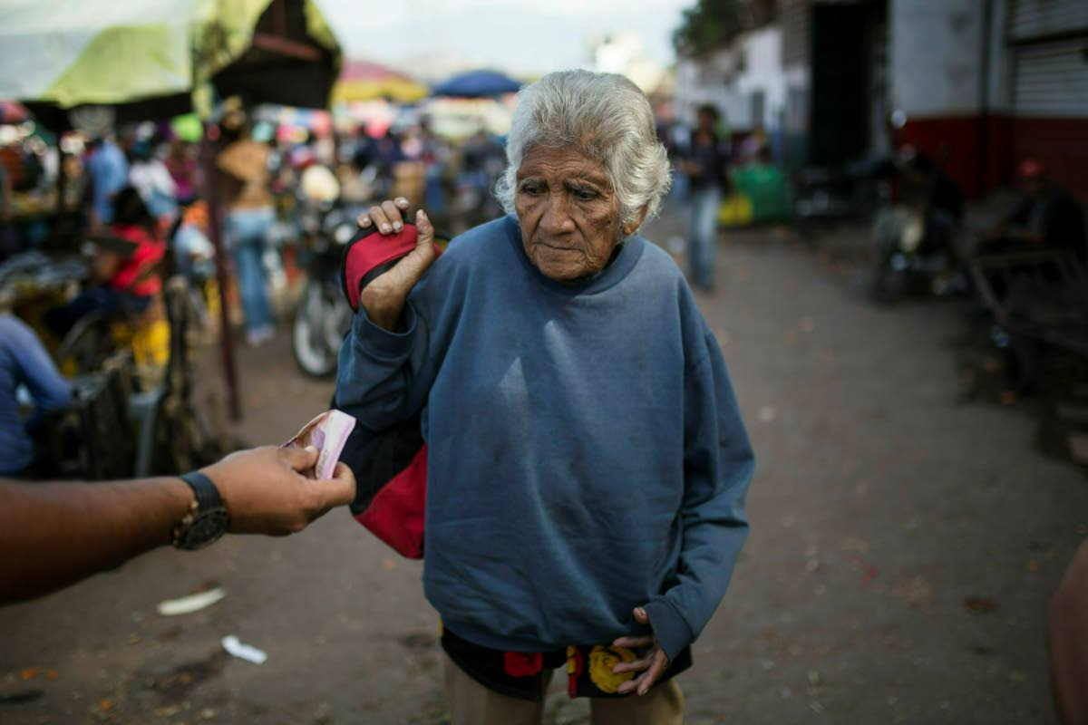 HARD TIMES: An elderly woman is offered cash as she begs at a wholesale food market in Caracas, Venezuela on Monday. AP PHOTO
