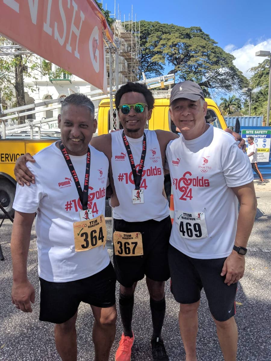 TTOC president Brian Lewis,centre, is flanked by Agriculture Minister Clarence Rambharat,left, and Mayor of Port of Spain Joel Martinez after they completed the TT International Marathon, on Sunday, at the Queen's Park Savannah.