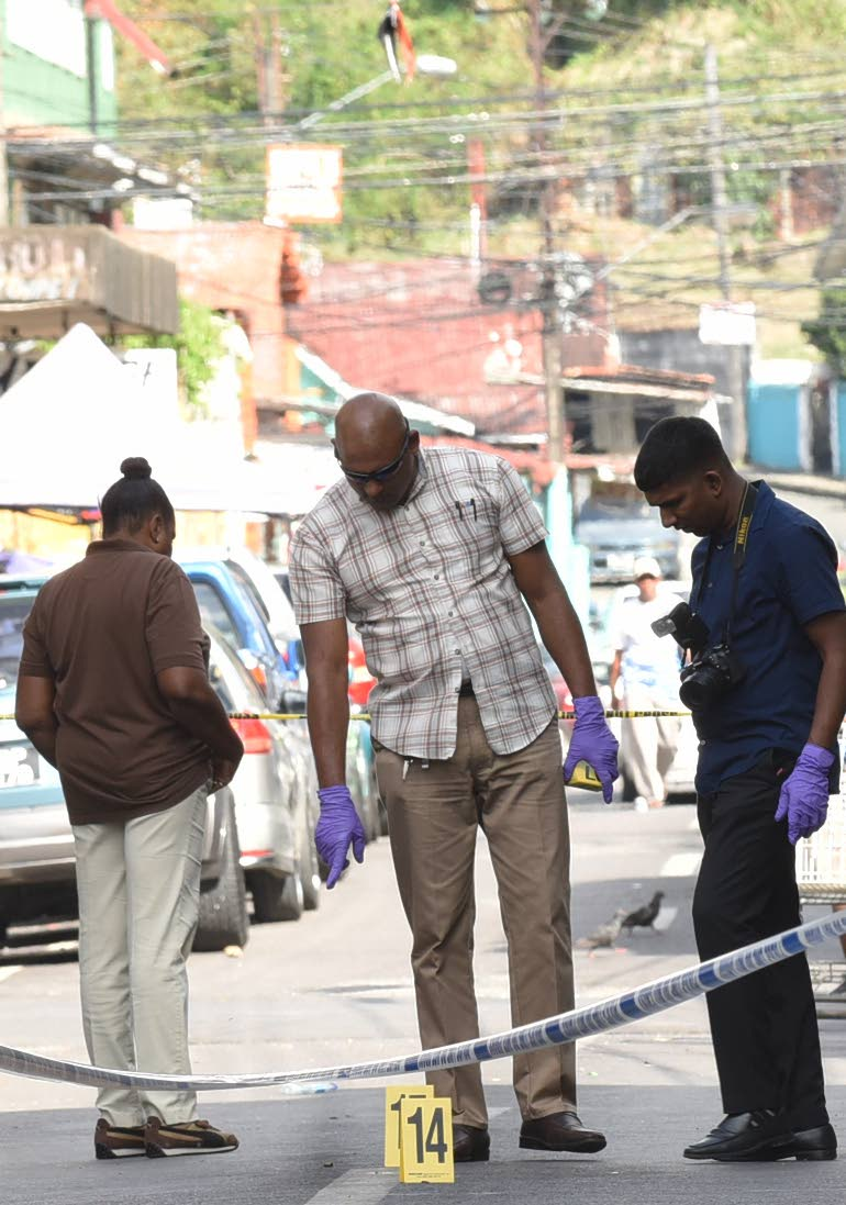 LOOK THERE: A policeman points to bullet casings strewn along Prince Street in Port of Spain following a shooting incident yesterday. PHOTO BY KERWIN PIERRE