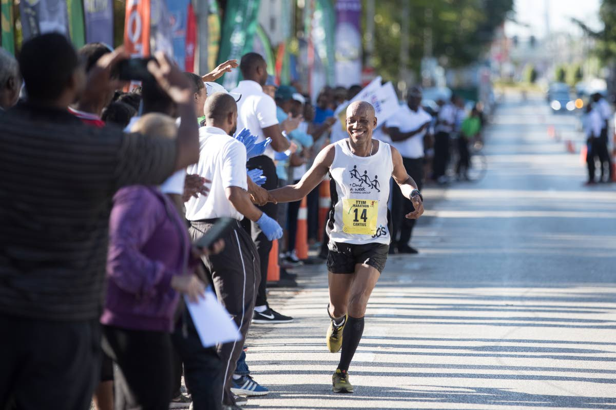 Cantius Thomas interacts with spectators as he approaches the finish line in the TT International Marathon on Sunday at the Queen's Park Savannah, Port of Spain. PHOTO BY ALLAN V CRANE/CA-IMAGES