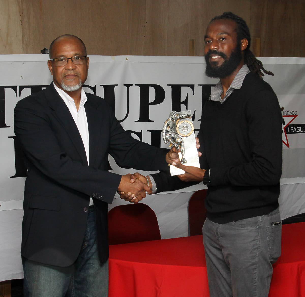 Super League president Keith Look Loy, left, presents the MVP award to Queen's Park defender Yohance Marshall at the league's awards ceremony at WASA Sports Club, St Joseph, last year. PHOTO BY ANGELO MARCELLE