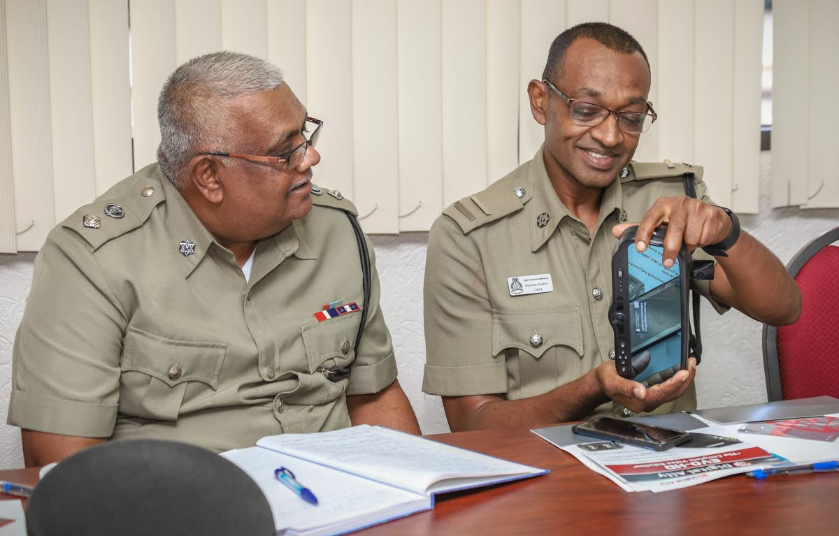 Traffic and Highway Patrol inspector Kissoon Badloo and senior superintendent Basdeo Ramdhanie examine a rear view mirror with camera which makes up part of the dashboard camera system.