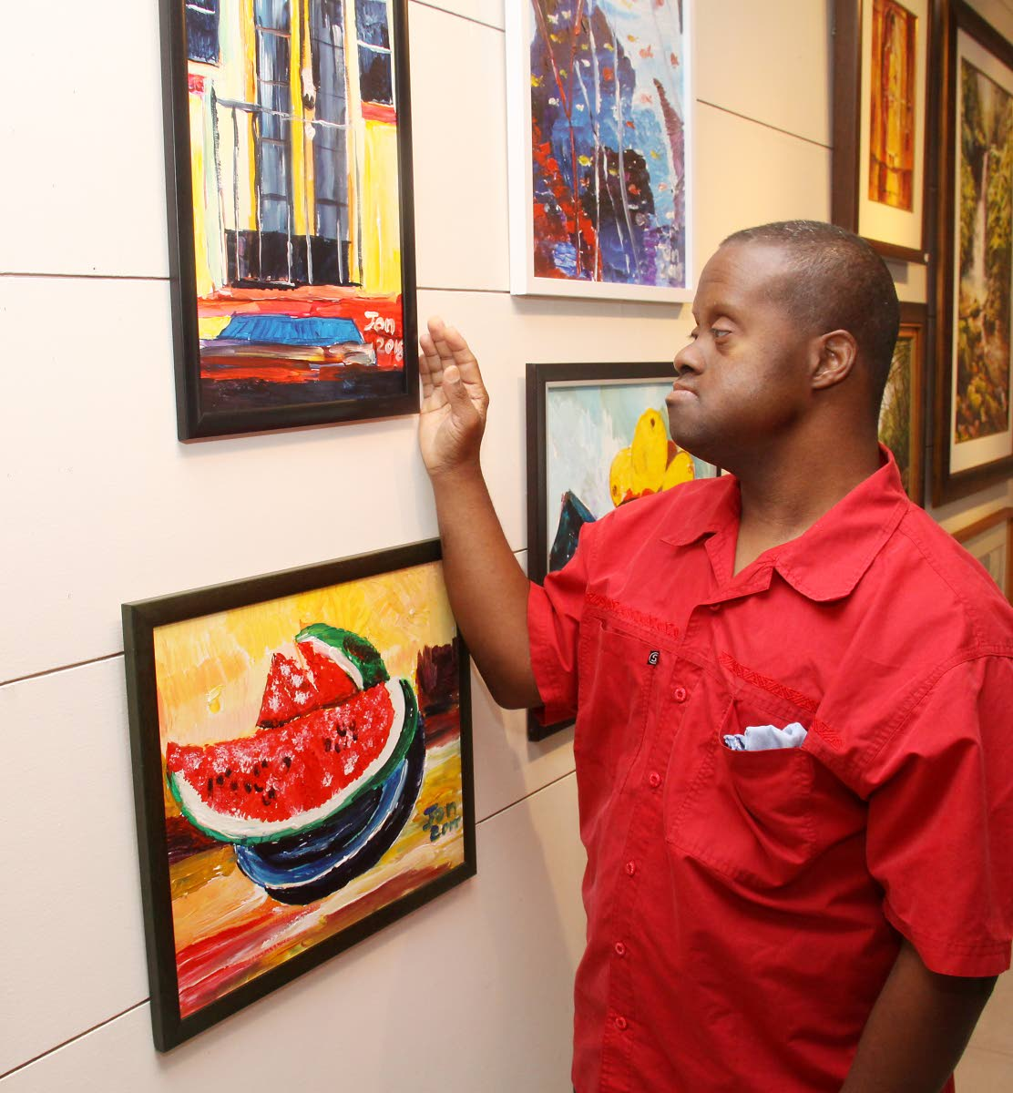 John Williams views his artwork, including his favourite one of a watermelon, at Horizon Art Gallery, Mucurapo. His second exhibition Dis-Is-Ability II runs from February 5 to 9. PHOTO BY ANGELO MARCELLE