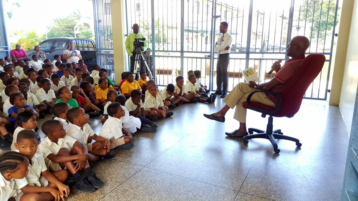 Prime Minister Dr Keith Rowley reads to students at the Carenage Government Boys School yesterday as part of World Read Aloud Day. PHOTO COURTESY THE OFFICE OF THE PRIME MINISTER