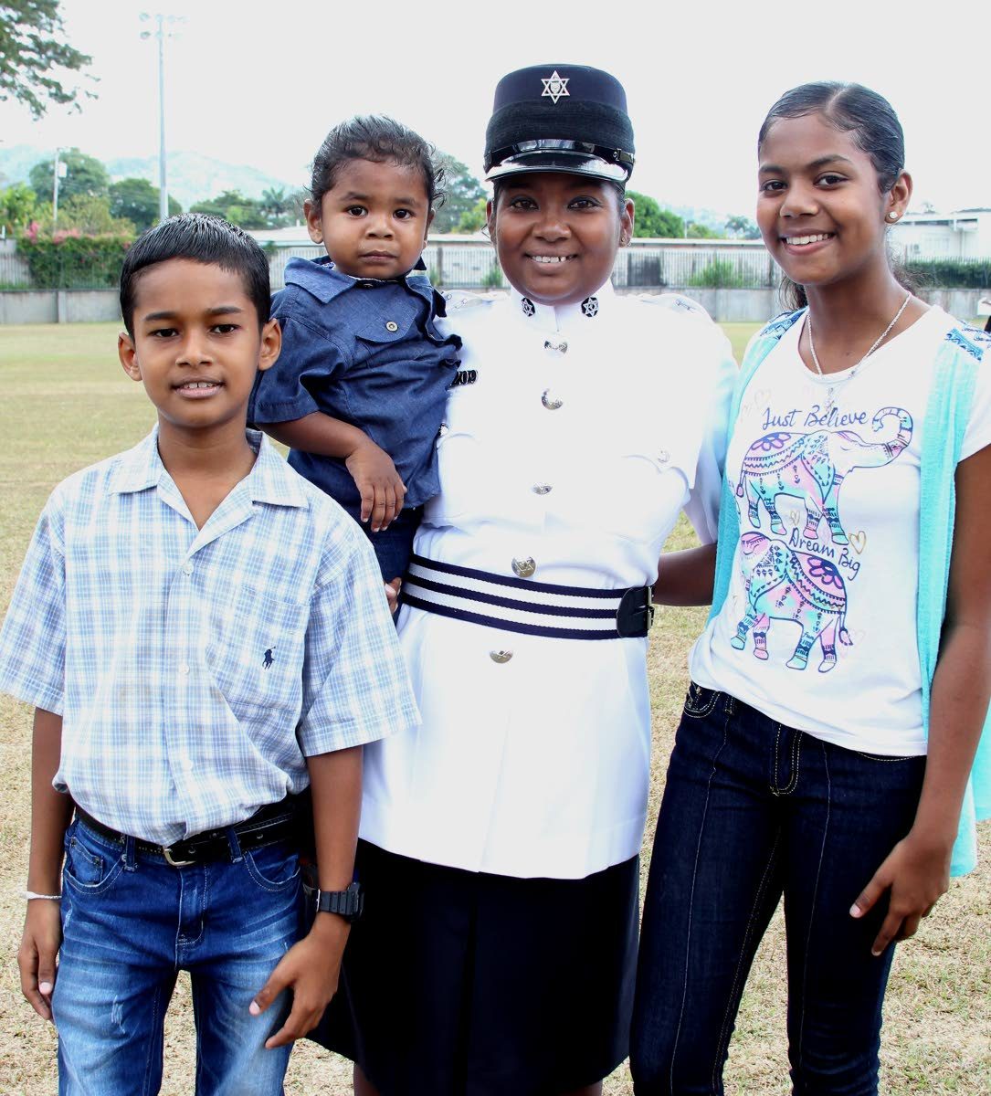 Natasha Gopee shares the proud moment she became a municipal police constable with her children Danesh, two, and Nandini, 13, and nephew Tristan, 10, after the passing out parade for municipal officers at the Police Academy, St James yesterday.