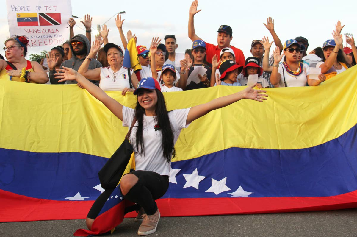 Venezuelans show their support for Juan Guaido as interim president of their country during a rally at Queen's Park Savannah, Port of Spain yesterday. PHOTO BY AYANNA KINSALE