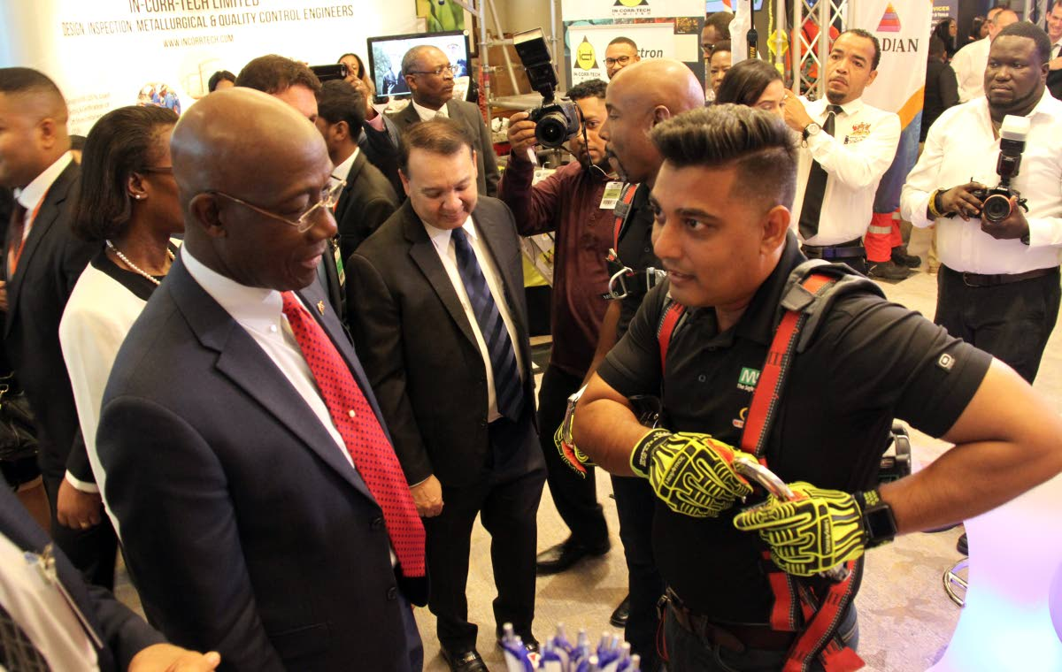 SECURE IT SO: IRP's Fire and Safety officer Farzul Ali shows Prime Minister Dr Rowley how to secure protective gear yesterday during the Energy Conference at the Hyatt Regency in Port of Spain. PHOTO BY SUREASH CHOLAI