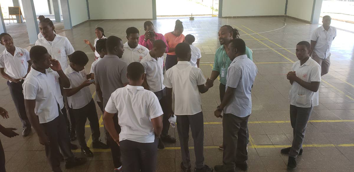 Former defender with the national football team, Brent Sancho, in green shirt, engages students of Mason Hall Secondary School during Monday'sCareer in Sports Caravan hosted by theTHADivision of Sport and Youth Affairs.