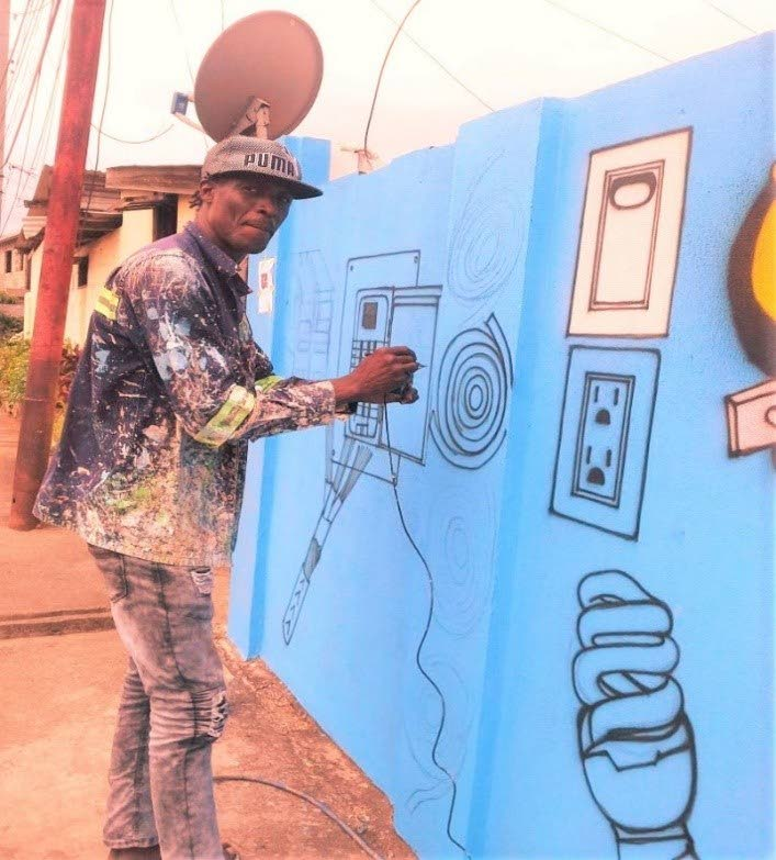 Everton McQueen works on a mural in Canaan.