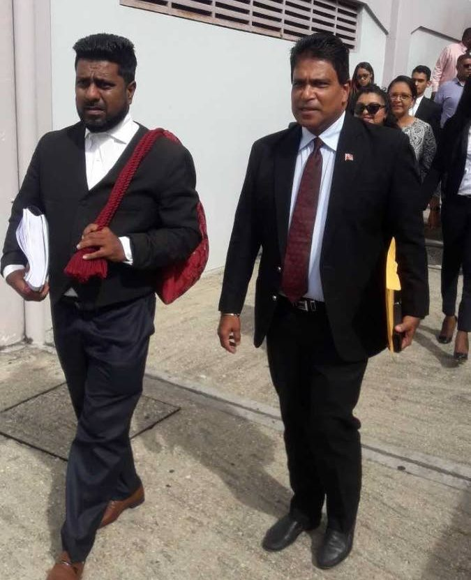 Oropouche East MP Dr Roodal Moonilal leaves San Fernando High Court yesterday with his attorney Gerald Ramdeen. Members of his constituency are in the background