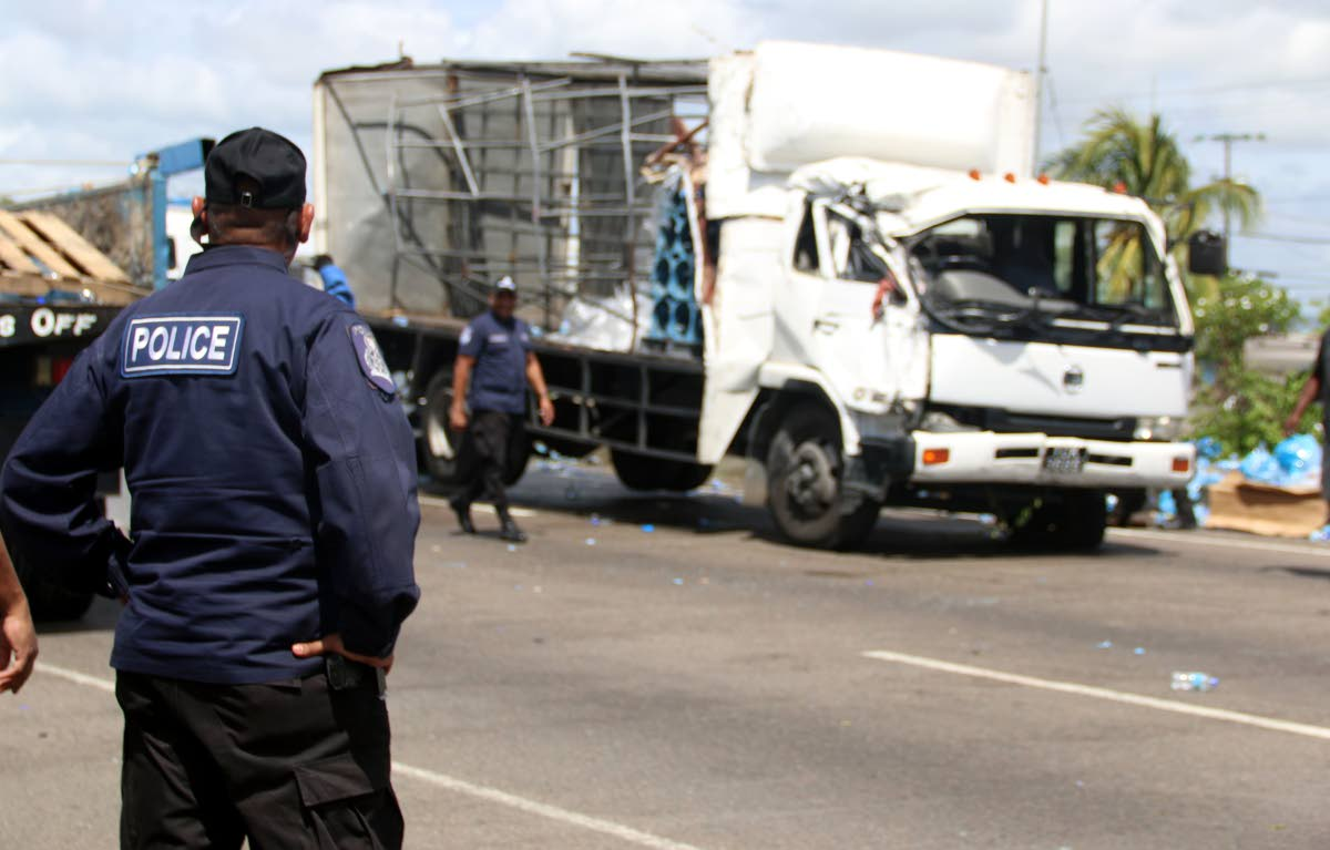 A policeman looks on at the scene of a collision involving a garbage truck, a Blue Waters truck and PTSC bus in which two women were killed on the Uriah Butler Highway, Chaguanas on February 5. PHOTO BY ANSEL JEBODH