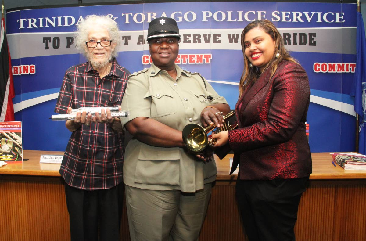 Legendary saxophonist Roy Cape, left, and Krystal Borris Bernard, music director of the Positive Movement Orchestra, right, present Assistant Commissioner of Police Patsy Joseph with a flute and trumpet respectively at the weekly police press briefing at the Police Administration Building yesterday. The instruments will then be handed over to the Oropune Police Youth Club.