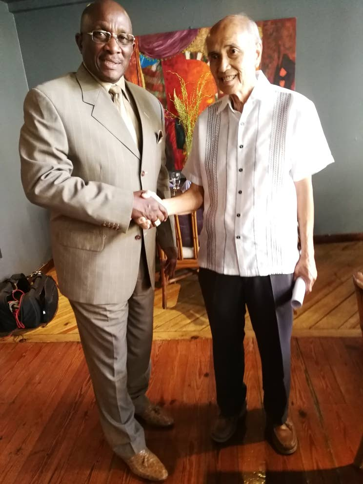 """Fred Chin Lee, owner of the new and improved Normandie, The Hotel at right, is greeted by Winston """"Gypsy"""" Peters , chairman of the National Carnival Commission, at the launch of the hotel's Under The Trees Carnival programme."""