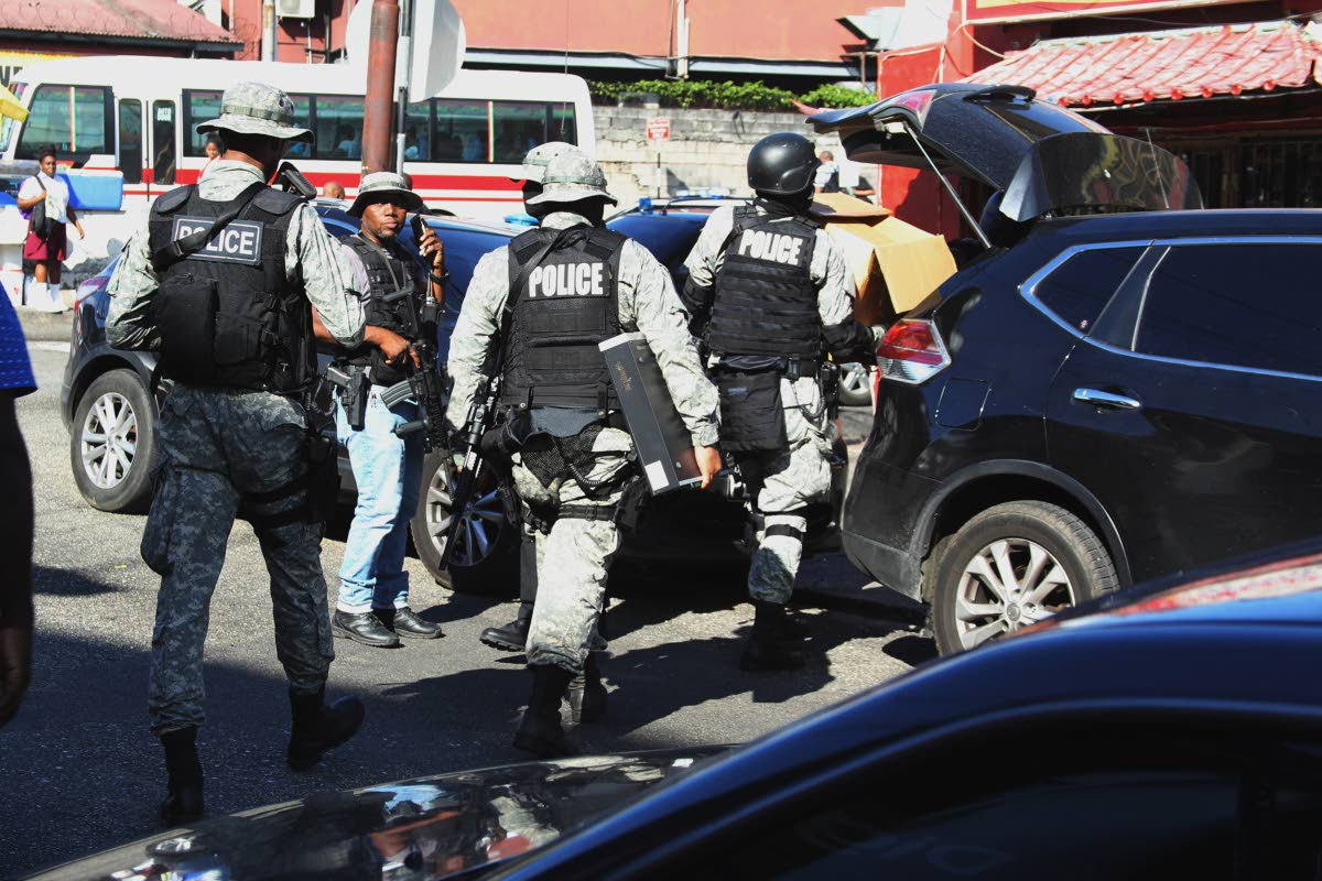 Members from the Special Operations Response Team, the Financial Intelligence Unit and Human Trafficking Unit, perform an extensive raid on Jamlong Members Club and JingDu Fast Food Resturant on Southern Main Road, Curepe, yesterday.