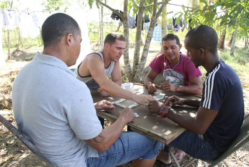 Some Cuban refugees play a game of dominoes at their temporary residence in Warrenville. PHOTOS BY AYANNA KINSALE