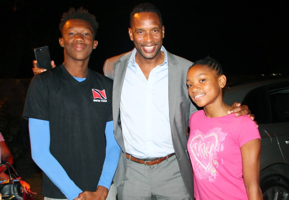 Shaka Hislop, centre, shares a light moment with two Flying Fish Swim Club members.