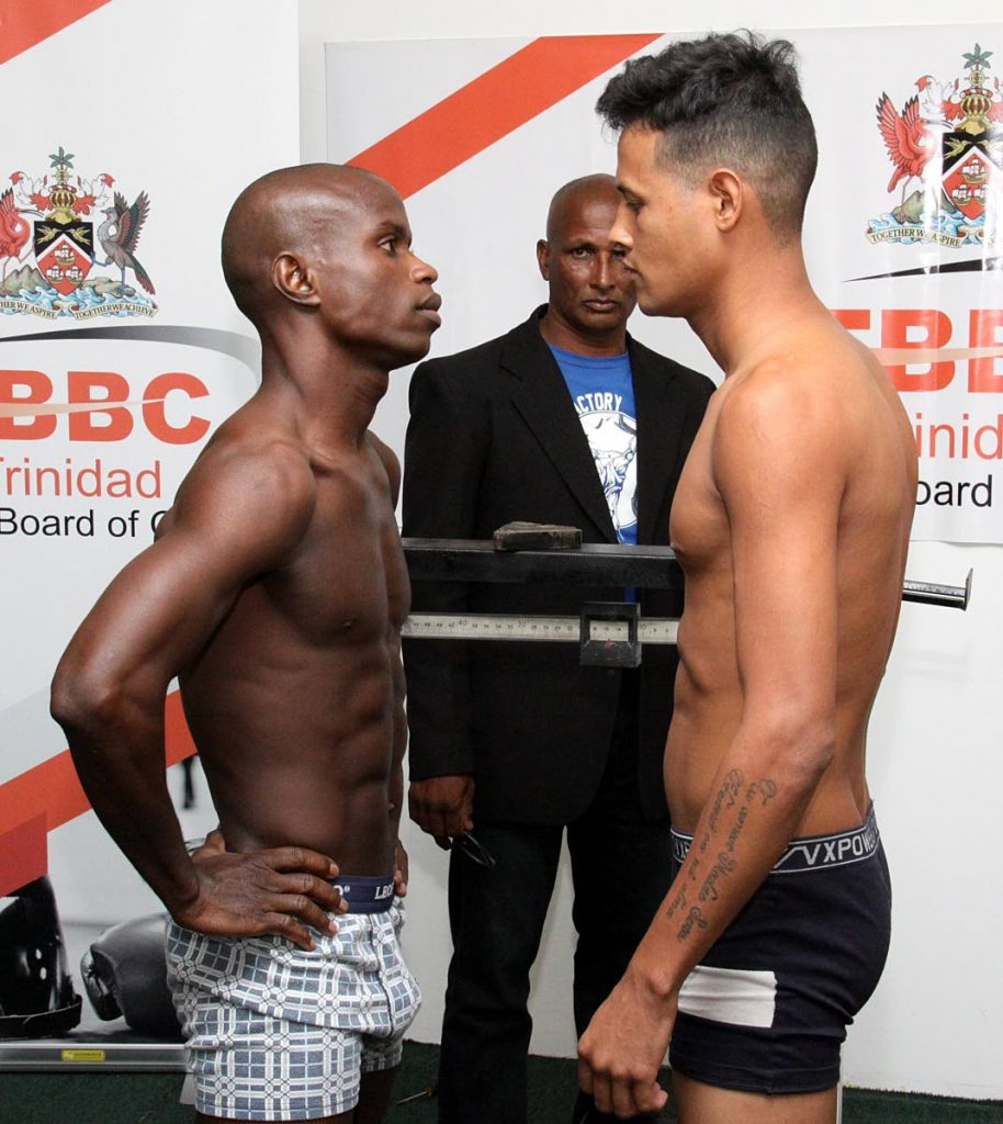 TT's Prince-Lee Isidore, left, stares down Venezuela's Antoni Armas at yesterday's weigh-in ceremony at the TT Boxing Board of Control office, Hasely Crawford Stadium, Mucurapo. PHOTO BY ANGELO MARCELLE