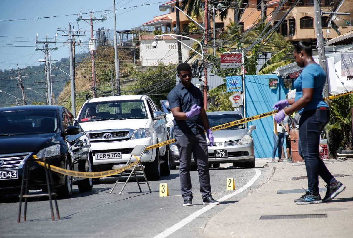 Investigators at the scene on Western Main Road, Caremange, near L'anse Mitan Road, where two women and an American teenage girl got shot while they were passengers in a car on Saturday morning. PHOTO BY JENSEN LA VENDE