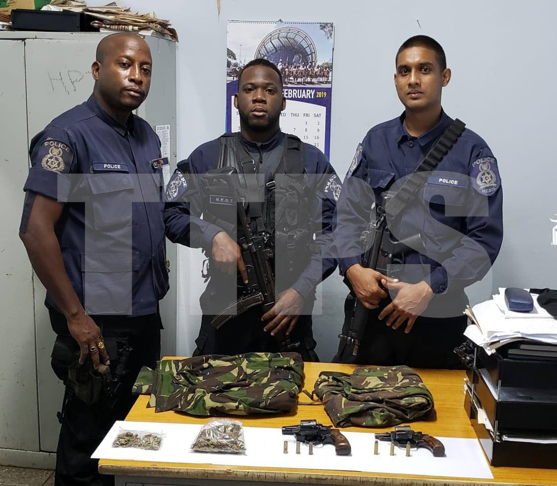 North Eastern Division officers with two guns, ammo and camouflage jackets seized during exercises overnight on Friday. PHOTO COURTESY TTPS