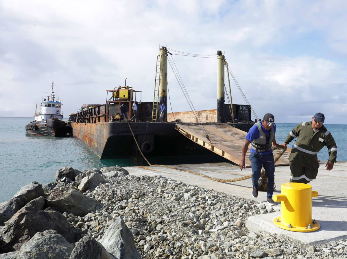 Barge operators at work at the Barbados Bay jetty at Studley Park Tobago on January 26.