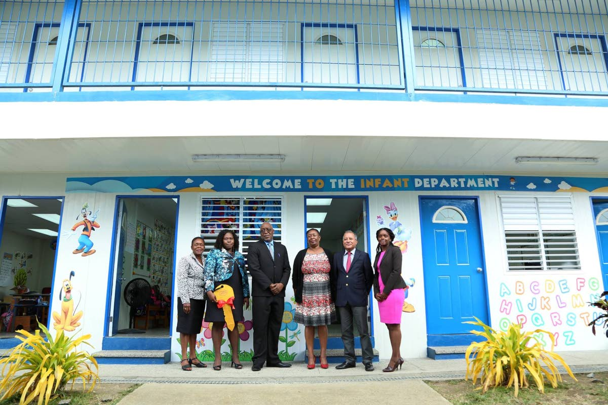 Chief Secretary Kelvin Charles, third from left, and Chris Jagroop, second from right, acting Chief Executive Officer, Udecott, stand in front of the newly constructed annex at Whim Anglican on Tuesday. Others in photo are from left, Karen Boatswain, School Supervisor II, Division of Education, Christine Benoit, Principal of Whim Anglican, Jacqueline Job, Administrator, Division of Education, and Janelle Berkley of Udecott.
