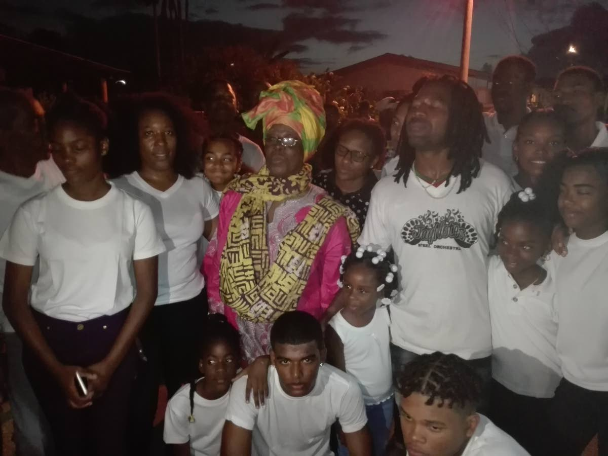 Jay Notes members with cultural icon Ella Andall, centre, at their pan tent on Guy Street, Sangre Grande, Thursday.