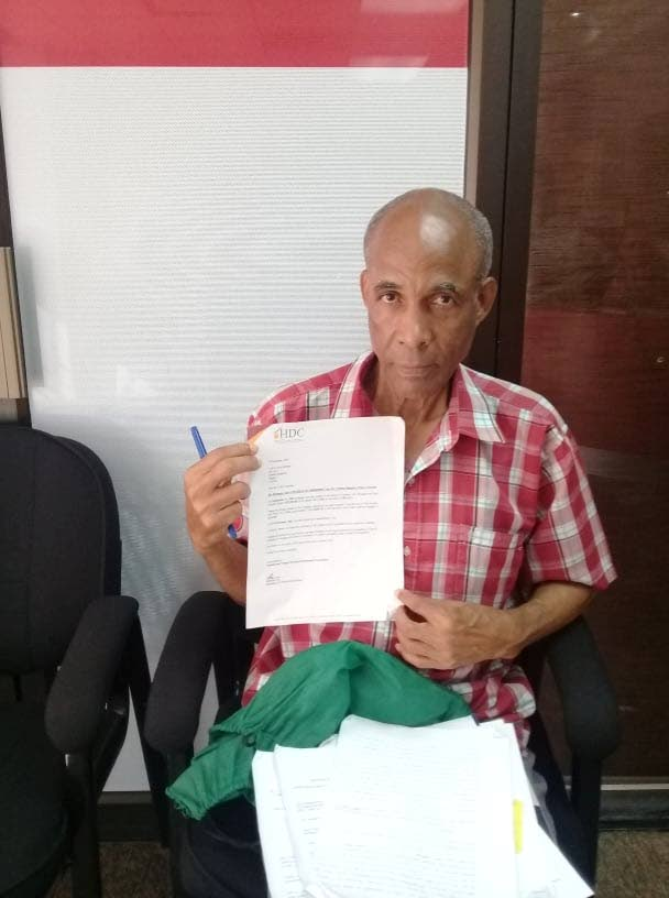Retired Part Authority worker Cyril Berkely holds up a document from the HDC acknowledging the receipt of his documents. Berkeley says he received several similar letters in response to his queries but is no closer to receiving the deed to a property he paid off for in 2002.