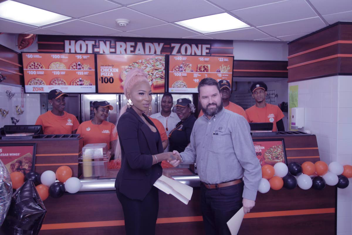 Soca singer Partice Roberts shakes hands with Rafael Moraga, the regional manager of Restaurant Holdings Limited (franchisees of Burger King, Popeyes and Little Caesars Pizza throughout the Caribbean). Roberts is now Little Ceasars brand ambassador.