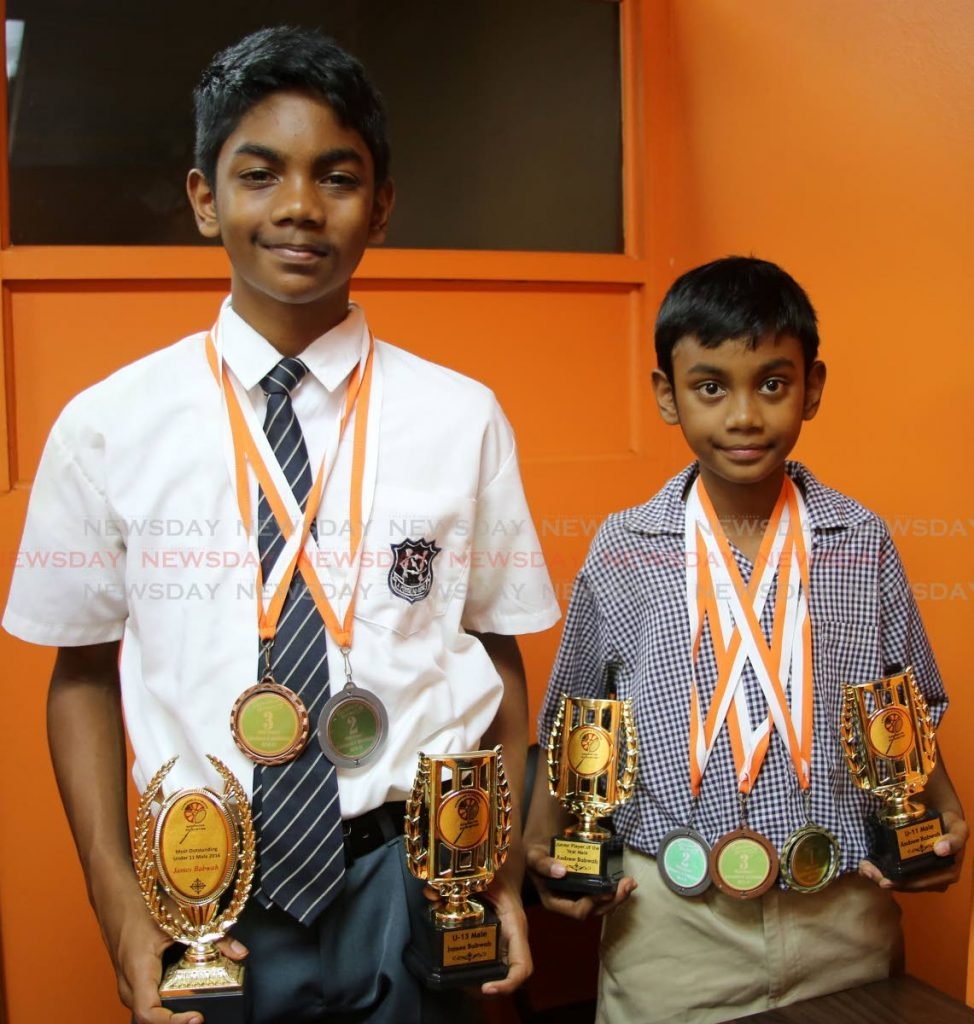 James Babwah, of Naparima College, and his brother Andrew, a student of Princes Town Presbyterian No 1, with the many medals and trophies they have won as badminton players. PHOTO BY VASHTI SINGH