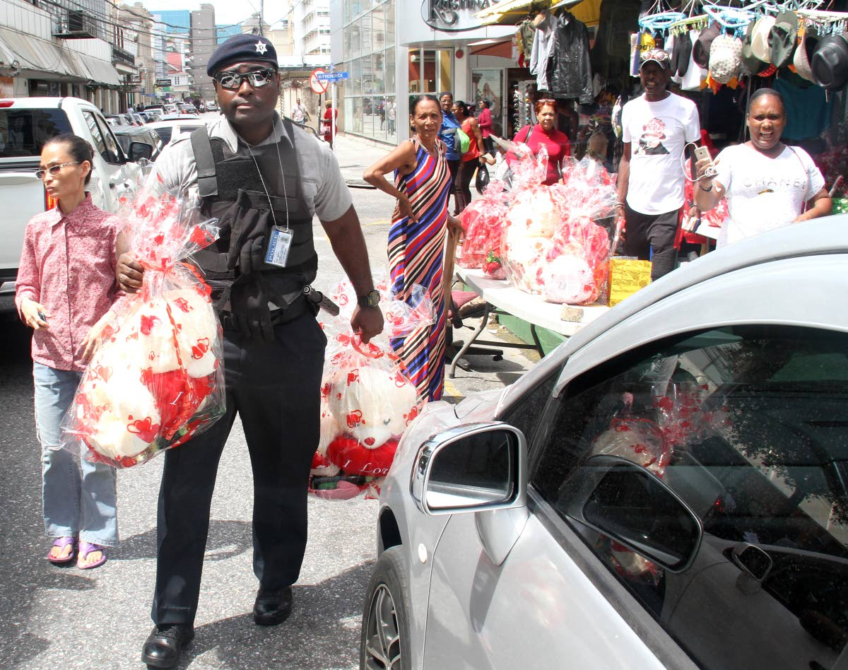 NO LOVE: A police officer leaves with Valentine's Day items from a vendor on Queen Janelle Commissiong Street yesterday. PHOTO BY AYANNA KINSALE