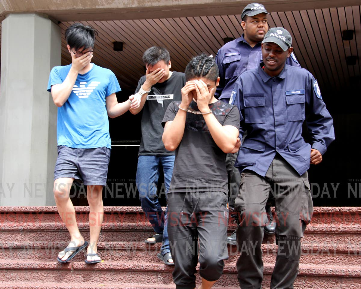 Police officers escort three Asian men out of the Hall of Justice, Port of Spain on Saturday morning after they appeared before a judge seeking release from custody as they have not been charged since their detention earlier this month. PHOTO BY SUREASH CHOLAI