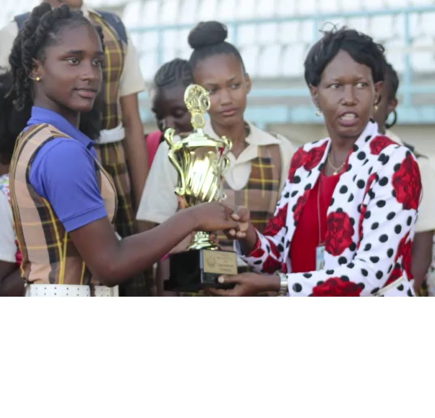 An athlete from Toco Secondary, left, is presented with a trophy at the Secondary Schools Relay Festival held on Thursday at the Larry Gomes Stadium, Malabar.