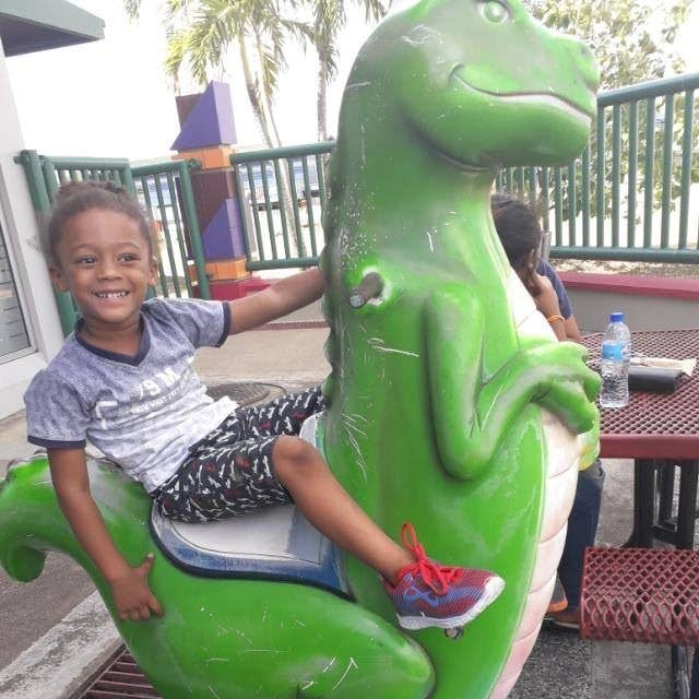 Prince Francette, 3, enjoys a ride on a dinosaur at a happier time.
