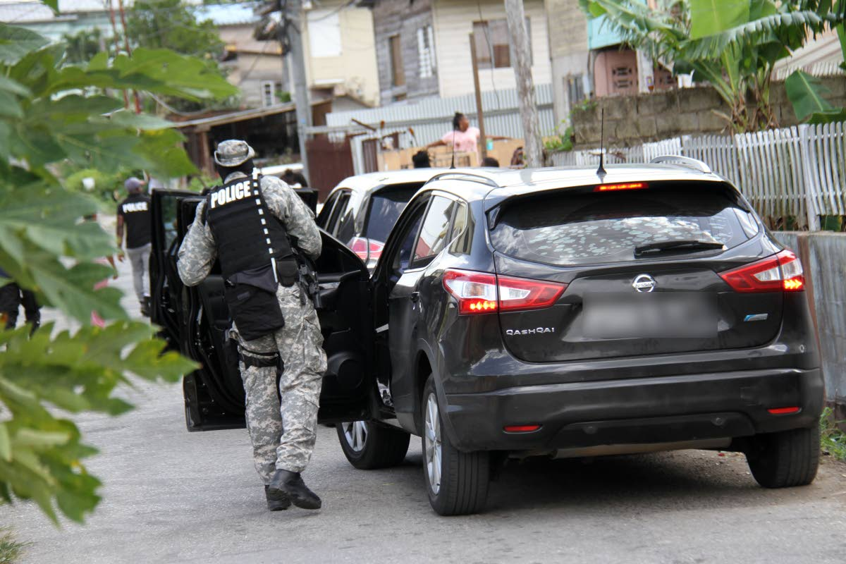 I REACH: A policeman arrives in La Romaine to join others in an anti-crime raid which later led to the arrest of 20 people and seizure of a number of illegal items. PHOTO BY CHEQUANA WHEELER