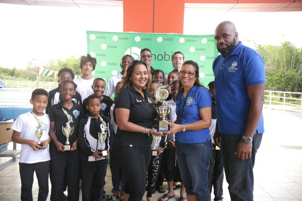 Anjanie Ramesar-Soom, front left, manager, corporate responsibility and community relations at TSTT, presents the trophy for the top team to Tidal Wave Aquatics' coach Hazel Haynes during the closing ceremony of Torpedoes Swim Team's first annual invitational long course competition recently. Looking on are Torpedoes' reconciliation officer Kevon Thomas, right, and members of Tidal Wave.
